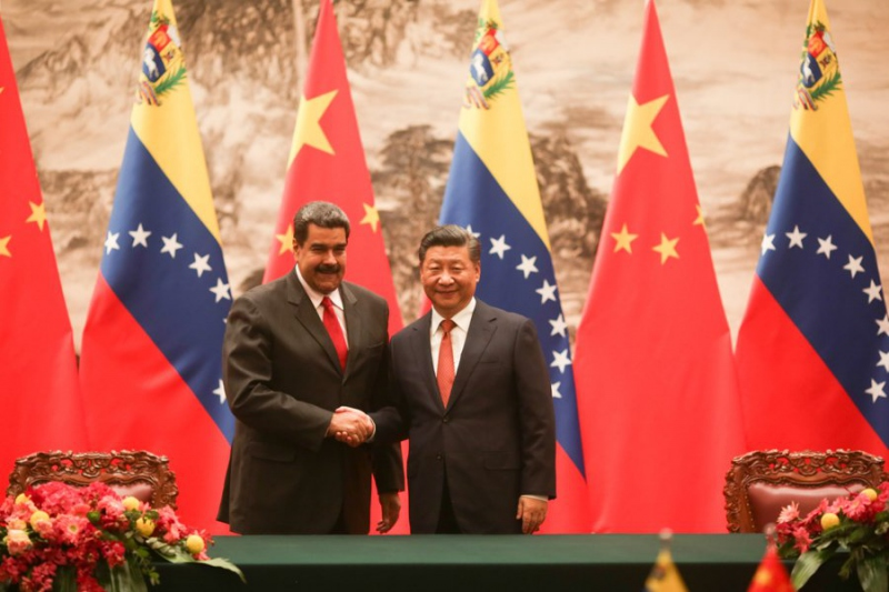 Venezuelan President Maduro (L) shakes the hand of Chinese President Xi Jinping during his state visit to China